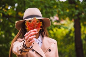 Woman with fall leaf in hand