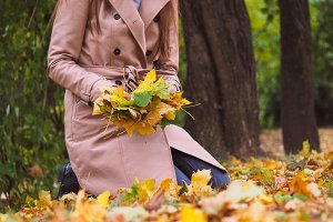 Woman with autumn leaves in hands