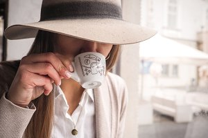 Woman with hat drinking coffee