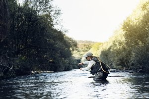 Fisherman using flyfishing rod.