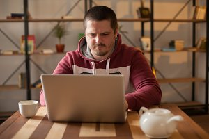 Man is sitting with grey laptop