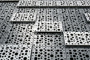 A wall of metal plates with holes in the sun.