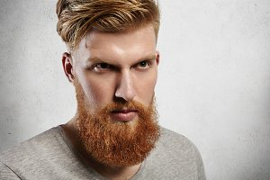 Harsh Caucasian man with perfect light skin looking ahead like a brave hero. His fringe is carefully styled and temples are shaved, well-trimmed ginger beard fits him well. Indoors studio shot.