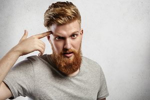 Young Caucasian macho man with blond beard and hipster hair-style pointing finger at his temple meaning ´Use your brain!ª. Handsome guy in grey casual T-shirt is surprised and slightly irritated.