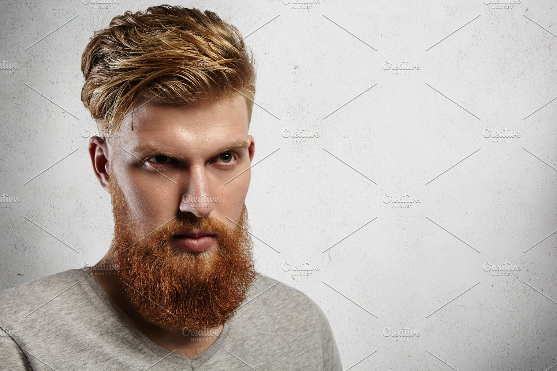 portrait of young european hipster with fair skin and trendy ginger beard.  fashionable undercut hairstyle and handsome face features together with