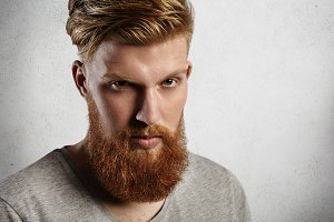 Young handsome and brave man looking at camera from under his blond eyebrows. European hipster in grey top with round crewneck, with nice ginger beard and moustaches looks stylish and trendy.