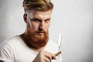 Headshot of attractive professional barber with thick red beard and mustache, holding razor. Young Caucasian hairdresser wearing white t-shirt standing in studio with cut-throat razor in his hands
