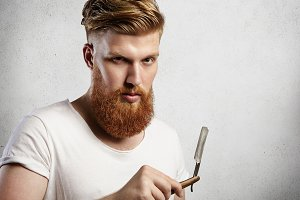 Young Caucasian hipster-like man in white T-shirt trying to decide whether to shave his long red-hair beard or not. Stylish guy holding straight razor with serious facial expression and look.
