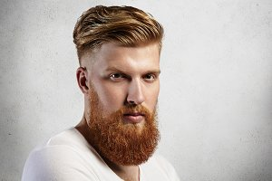Sideways portrait of natural blond Caucasian man on white background. Bearded hipster with clean shaved temples and stylish well-trimmed moustaches looking serious and brutal with long facial hear.