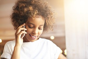 Attractive fashionable dark-skinned girl with Afro haircut wearing white t-shirt having phone conversation with her boyfriend, looking down with flirting smile while relaxing at cozy coffee shop