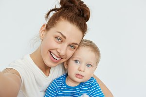 Nice selfie of mother and child on white background. Young Caucasian woman with blue eyes, smiling, holding in her arms little blond boy in blue stripped T-shirt. Happy family self-portrait.