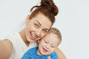 Positive family selfie with young mommy and toothless kid smiling together on white background. Playful state of mind and happy mood of attractive woman makes this shot fabulous, heartwarming.