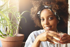 Portrait of African American young woman with Afro haircut dressed in white stylish denim shirt, holding cup of hot coffee or tea looking at camera with happy face, having nice time at cafeteria
