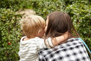 Mother and kid walking in the garden. Lovely pair of blond and brunette cuddling, kissing outside in green bushes. Five-years old boy putting arm around woman's neck. Sharing love concept.