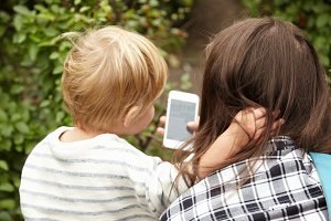 Backside portrait of mother and son outside. Blond hair of little boy making contrast with brown hair of woman. Two persons looking at smartphone with interest, kid hugging woman around her neck.