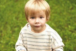 Charming close-up innocent portrait of little innocent kid. Calm Caucasian boy with blond hair, round brown eyes looking at camera. Five-years old infant standing still on fresh green grass background.