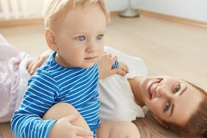 Positive shot of blue-eyed mother and her son playing on the floor of their bedroom. Cute toddler sitting, looking ahead with his big innocent childish eyes. Young mommy smiling on the floor.