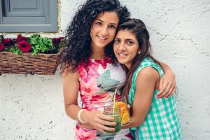 Two women with beverages looking at camera embracing