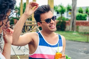 Happy man with sunglasses laughing in summer party