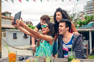 Young people taking a selfie with tablet in party