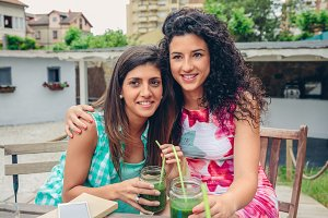 Two women embraced with smoothies looking at camera