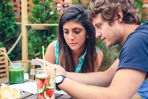 Young couple looking smartphone outdoors in summer