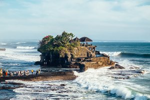 Outdoors sea view near Tanah Lot temple with line of people, Bali. Indonesia nature landscape in sunny daylight