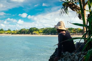 Local man in a hat sitting under palm tree and watching the beautiful blue sea of Nusa Dua, Bali, Indonesia. Explore Asia relax landscape