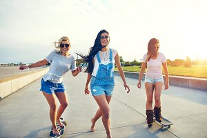 Three young woman skateboarding at the beach