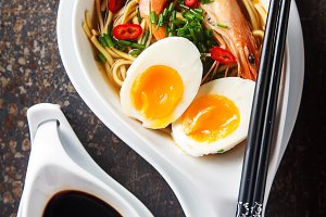 Miso Ramen Asian noodles with egg, shrimp, green onions, chili peppers in a white bowl. Dark background. Top view