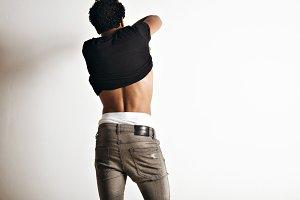 Hot latino young man taking off his t-shirt