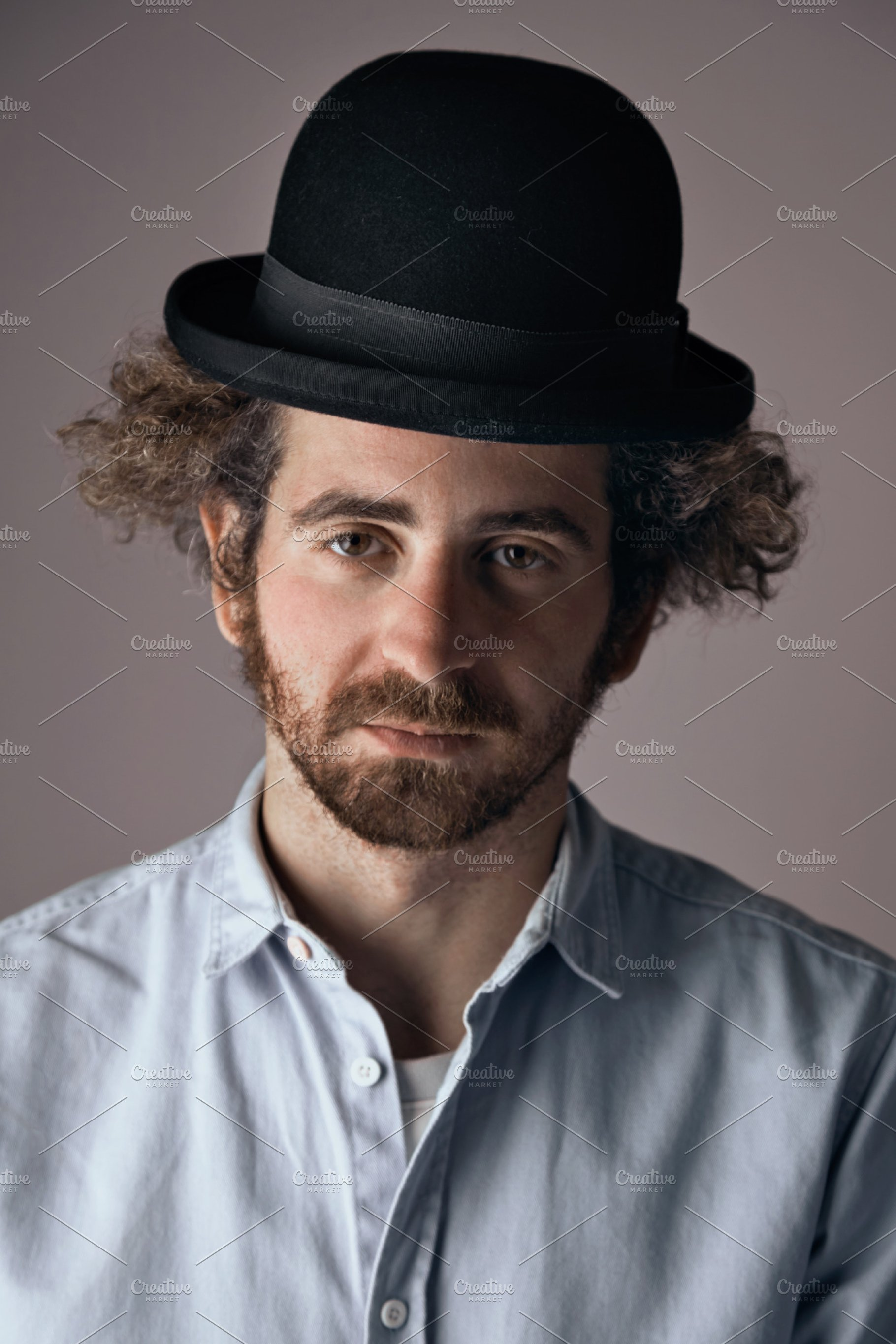 Sad bearded man with curly hair in black hat