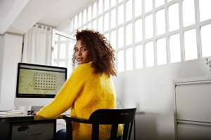 Young beautiful black girl works in home office