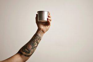 Tattooed hand with metal travel cup