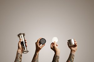 Four tattooed hands holding aeropress parts