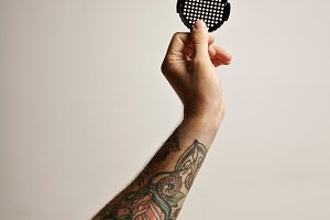 Tattoed arm and hand with aeropress filter cap