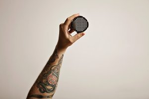 Tattooed man's hand holding aeropress filter cap
