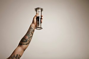 Hand with tattoos holding aeropress