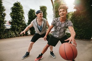 Happy teenagers playing basketball
