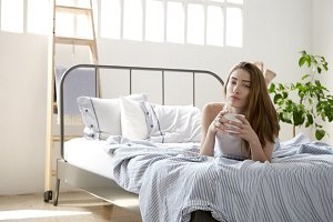 young woman in loft in bed