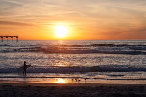 Surfer by the Ocean at Sunset