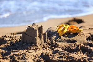 sand castle and children's flip-flops for beach
