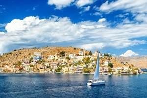 sailing yacht in the beautiful buildings of Symi island, Greece, clouds, sky, bright Sunny day