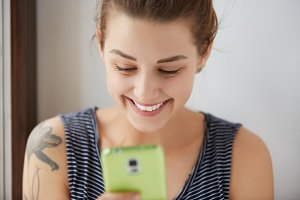 Close-up portrait of dark-haired female with white skin sending messages to her friends in the internet. Social communications through our gadgets can be really funny and joyful. Positive concept.