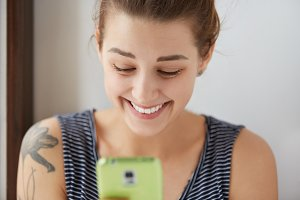 Happy European female chatting in social networks with her friends. Young attractive girl with shiny smile laughing at jokes from messenger, texting back sms to friends with her green digital device.