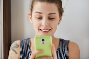Close-up portrait of European girl playing games at her green smartphone. Young and charming woman holding her gadget with two hands, looking at display with slight smile. Indoors daylight shot.
