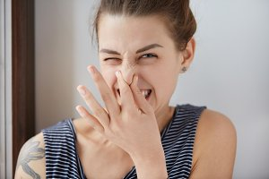 Close-up shot of Caucasian girl showing disgust, pinching her nose to avoid bad smell. Brunette girl with bunch of hair narrowing eyes in aversion to awful stink. Negative emotions, nasty feelings.