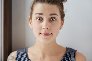 Stylish shot of surprised scared Caucasian girl with brown hair, charming blue eyes, white skin. Young female with tattoo looks lovely in her natural amusement with closed mouth, raised eyebrows.