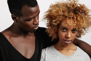 Stylish portrait of young Afro-American couple on white background. Cute girl with big brown eyes and wavy short hair bravely looking at camera. Manful guy staring at her, putting hand over her neck.