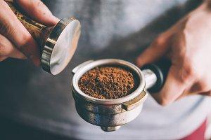 Barista presses ground coffee